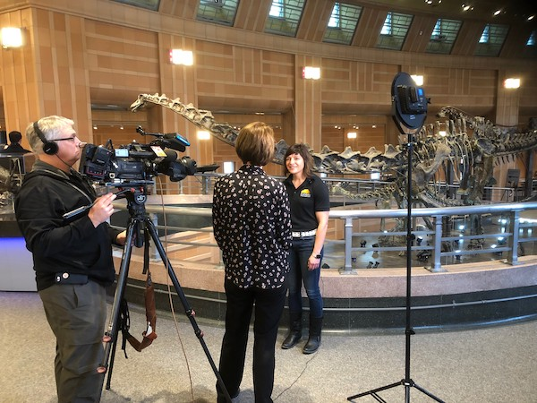 Sarah Lima gives an interview in front of a dinasaur skelton