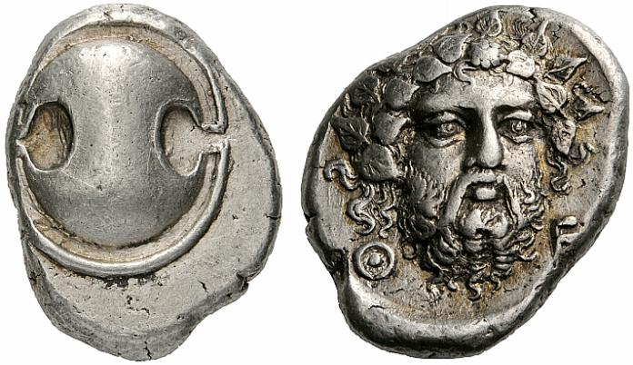 silver Theban Stater coin showing a Biotian Shield on the obverse (front) and a depiction of Dionysus on the reverse (back)
