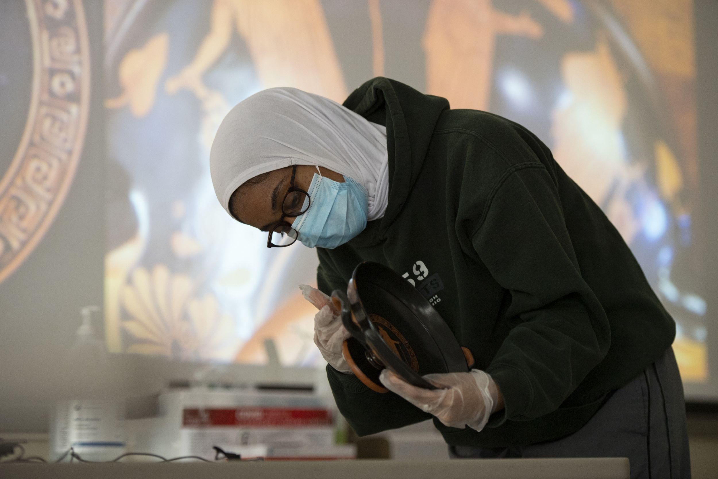 a student wearing gloves inspects a kylix
